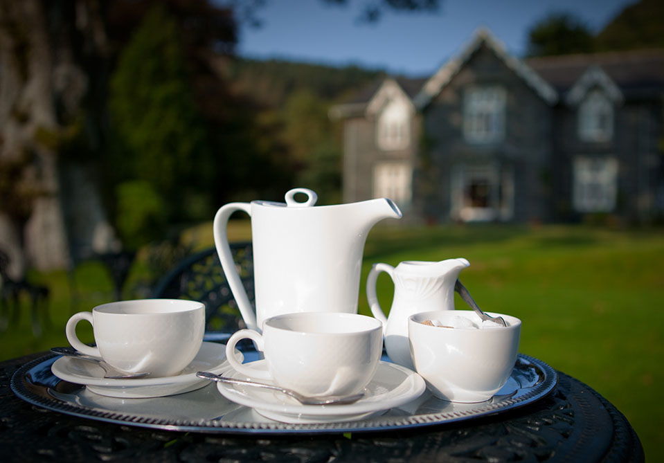 Exterior photo of Hazel Bank hotel with cups of tea arranged on the table