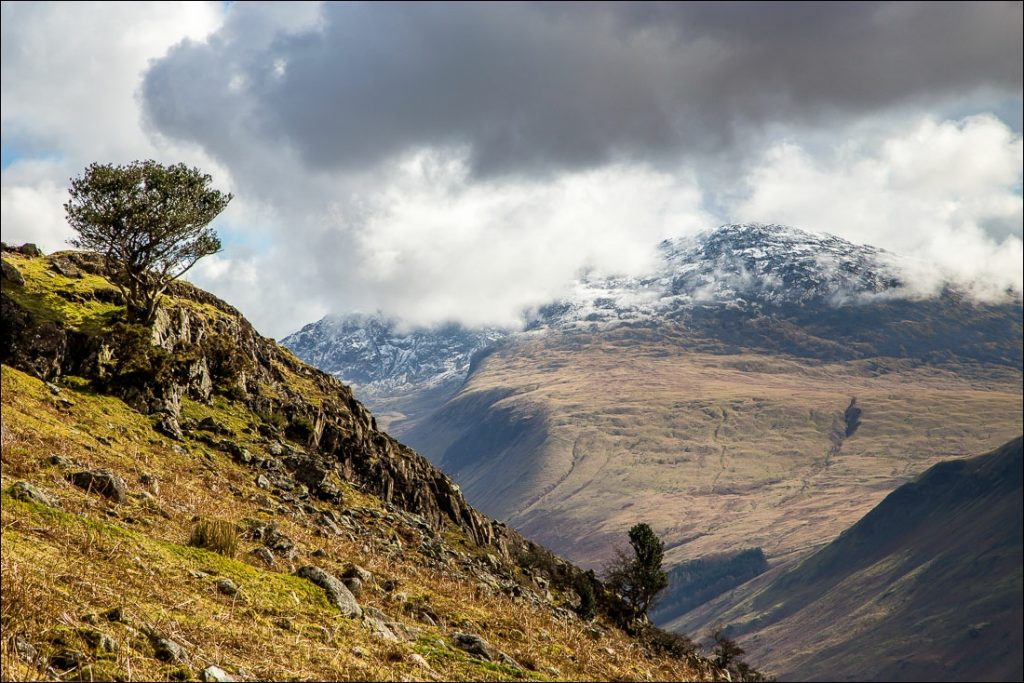 The Scafells snow capped with rugged terrain in the foreground.