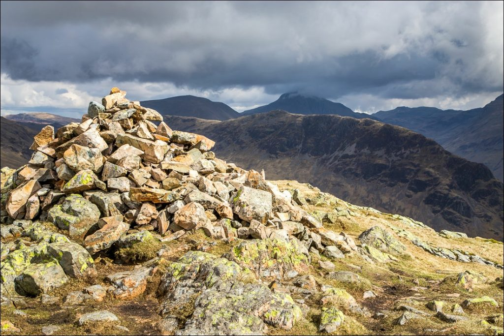 The summit cairn of Middle Fell and faraway fells shrouded in cloud in the background.