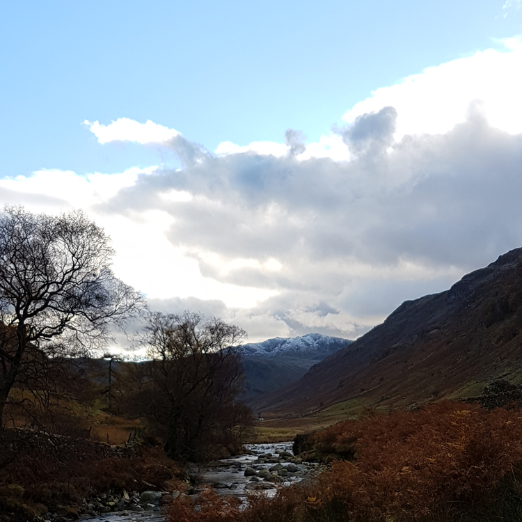 Looking down the Borrowdale valley toward snow-capped fells ion a walk in Borrowdale